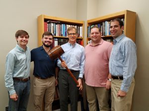 Mock trial team posing with a large gavel