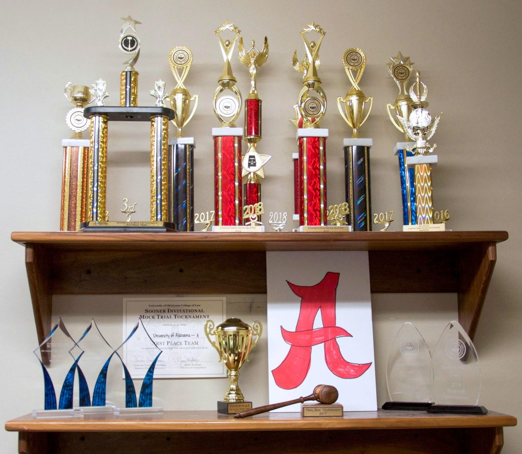 shelves displaying several trophies won by the UA Mock Trial team