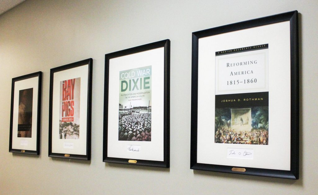 an assortment of framed images of book covers hanging in a hallway